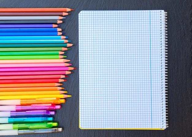 Terug naar school potloden regenboog en geregeerd notitieboekje, bovenaanzicht
