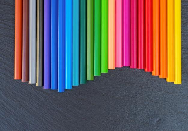 Terug naar school potloden regenboog grens op zwarte achtergrond, bovenaanzicht