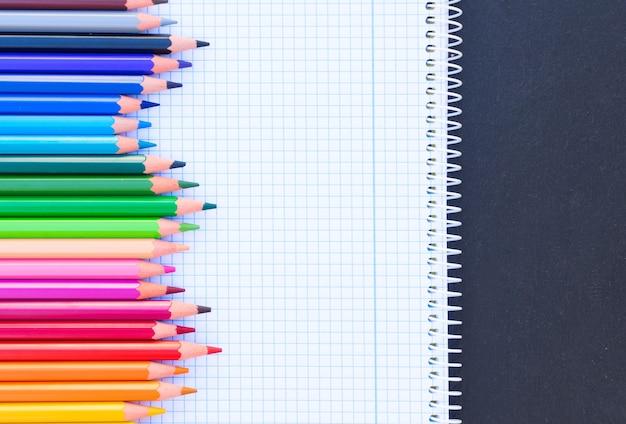 Terug naar school potloden regenboog op gelinieerd papier van notebook