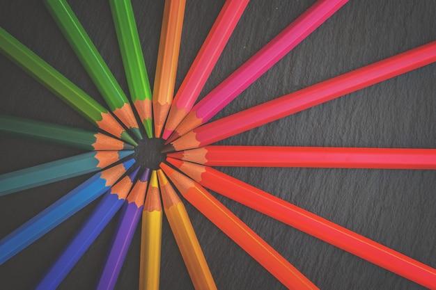 Terug naar school potloden regenboog op zwarte achtergrond, retro afgezwakt