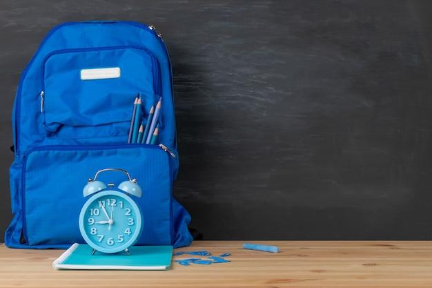 Terug naar school. rugzak, wekker en boeken hemelblauwe toon op klaslokaalbureau met bordachtergrond.