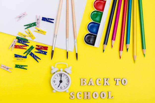 Terug naar school. schilderbenodigdheden, wekker en inscriptie in houten letters op een gele achtergrond. bovenaanzicht