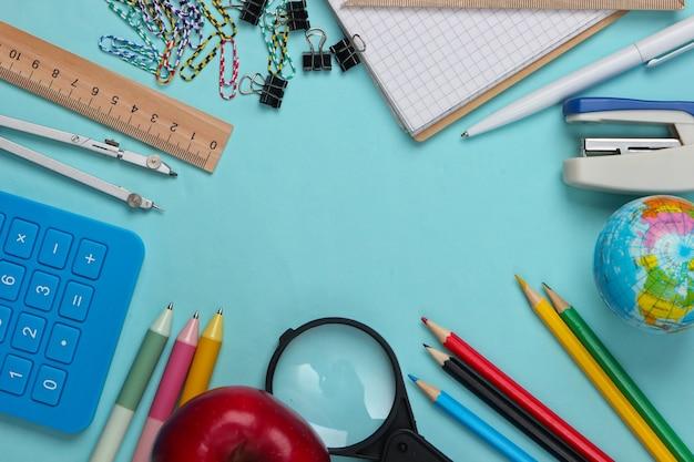 Terug naar school. school en bureaulevering op blauw. educatief, studieconcept. kopieer ruimte