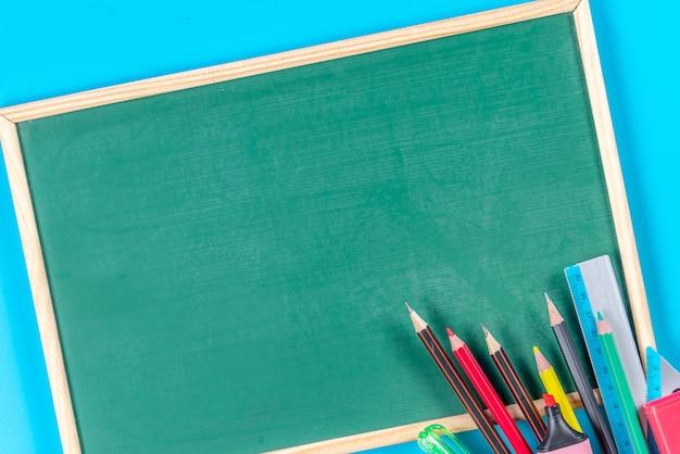 Terug naar school . schoolbenodigdheden en groen schoolbord op blauw