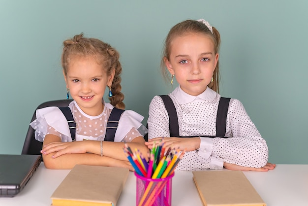 Terug naar school schoolmeisjes schrijven tekenen in een notitieboekje zittend aan de tafel en huiswerk maken