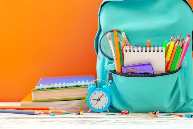 Terug naar school. schoolrugzak met verschillende leveringen en wekker op oranje achtergrond