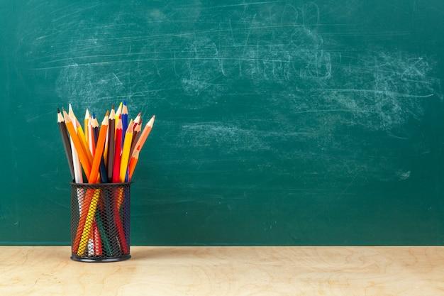 Terug naar school sjabloonontwerp, met schoolbenodigdheden, greenboard achtergrond