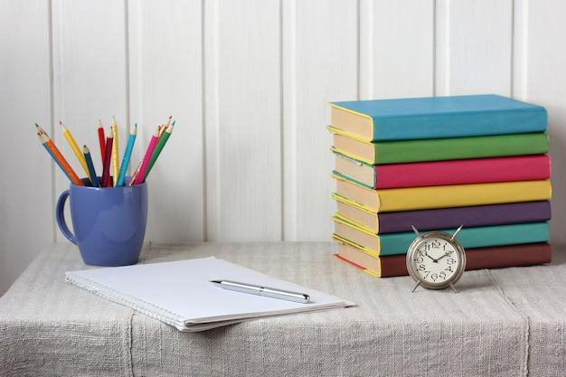 Terug naar school. wekker, kleurpotloden en leerboeken.