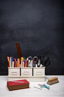 Terug naar schoolachtergrond met boek, potloden, kleurpotloden, krijt en andere benodigdheden op zwart