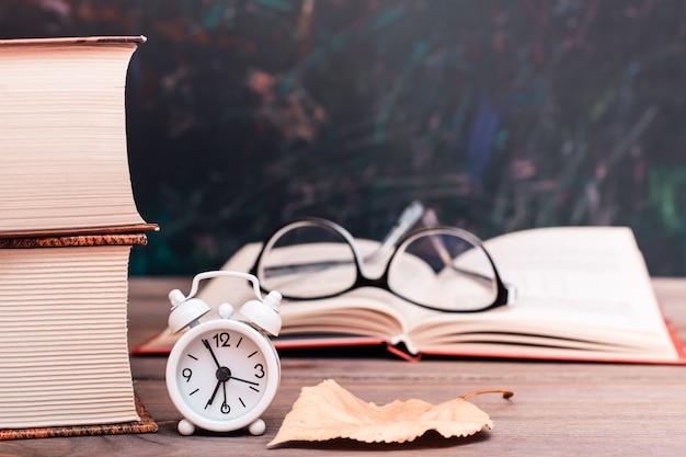 Terug naar schoolachtergrond met boeken en klok