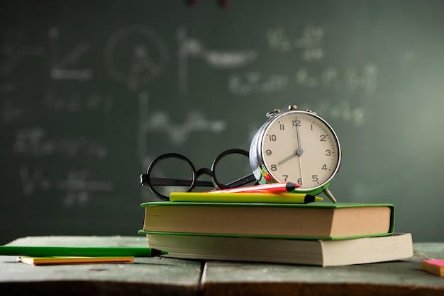 Terug naar schoolachtergrond met boeken en wekker over bord. terug naar schoolconcept