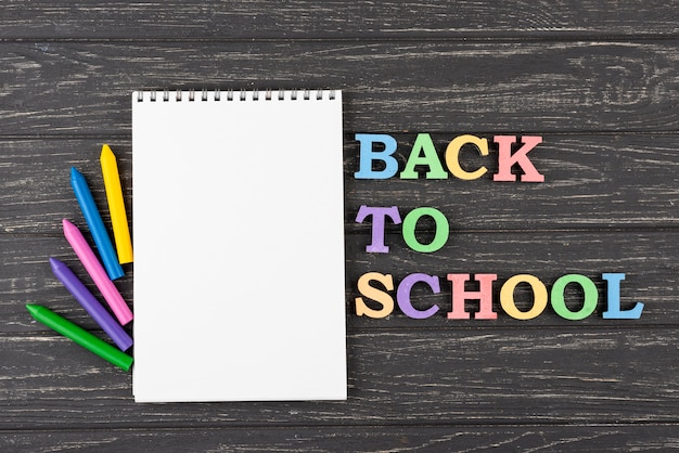 Terug naar schoolachtergrond met kleurpotloden en notitieboekje