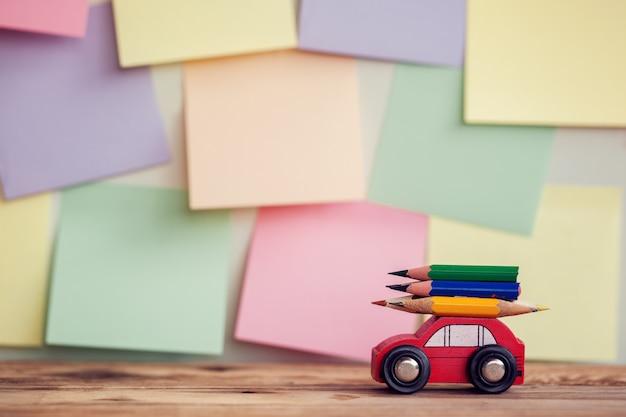 Terug naar schoolachtergrond met miniatuur rode auto die kleurrijke potloden over kleurrijke stikers op muur dragen