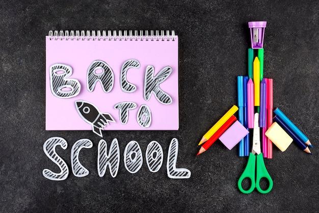 Terug naar schoolachtergrond met rocketship en notitieboekje