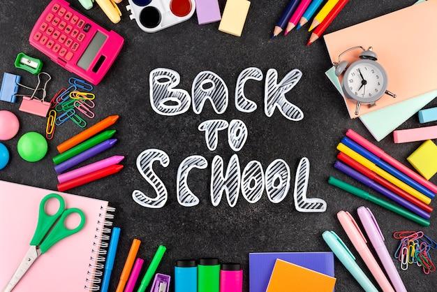 Terug naar schoolachtergrond met schoolbenodigdheden en een klok