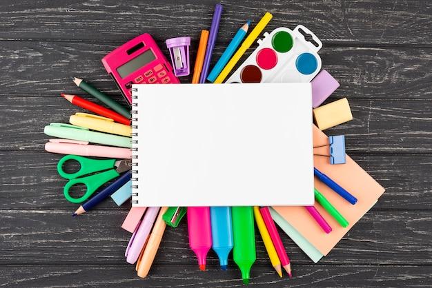 Terug naar schoolachtergrond met schoolbenodigdheden en exemplaarruimte op notitieboekje