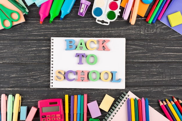 Terug naar schoolachtergrond met schoolbenodigdheden en notitieboekje