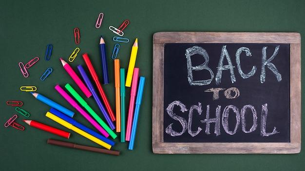 Terug naar schoolachtergrond met schoolbenodigdheden op bord
