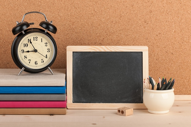 Terug naar schoolachtergrond met wekker, bord en potloden op tafel