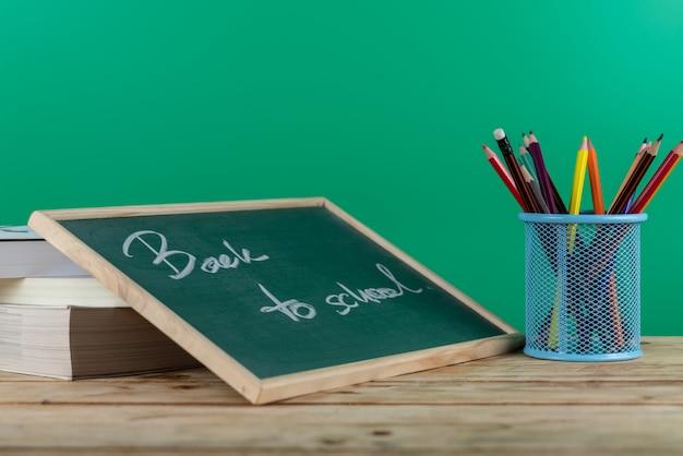 Terug naar schoolbrief in bord met kleurenpotlood in houder op de lijst