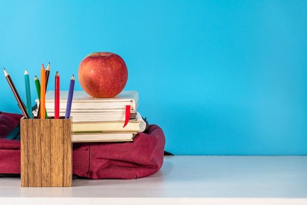 Terug naar schoolconcept. appel en schoolbenodigdheden op witte tafel