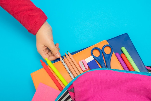 Terug naar schoolconcept de kindhand neemt schoollevering van rugzak op gekleurde achtergrond