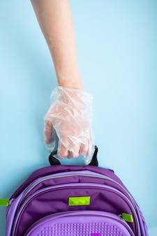 Terug naar schoolconcept. het concept van coronavirusinfectie, quarantaine op scholen, een gehandschoende hand die een schooltas vasthoudt