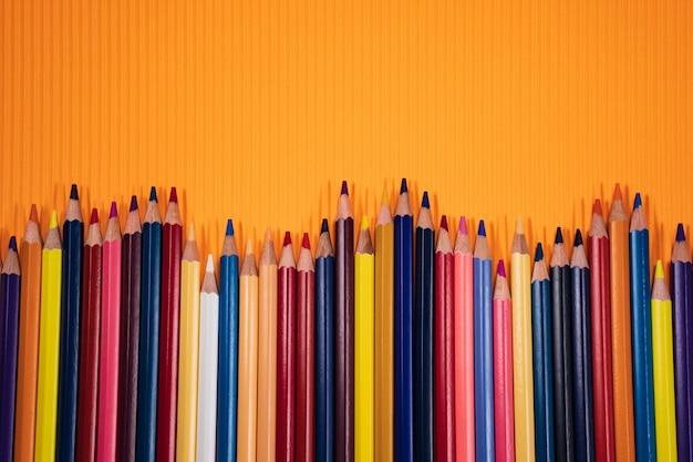 Terug naar schoolconcept. kleurenpotloden op oranje achtergrond.