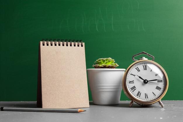 Terug naar schoolconcept met alarm, cactus en groen bord