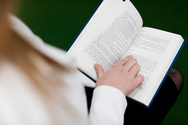 Terug naar schoolconcept met dichte omhooggaand van vrouw die in bibliotheek bestuderen