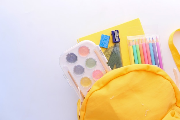 Terug naar schoolconcept met gele rugzak en schoolleveranciers op tafel.