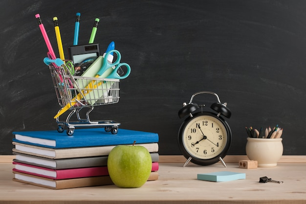 Terug naar schoolconcept met schoolbenodigdheden en wekker