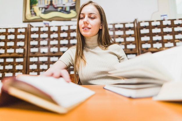 Terug naar schoolconcept met vrouw die in bibliotheek bestudeert