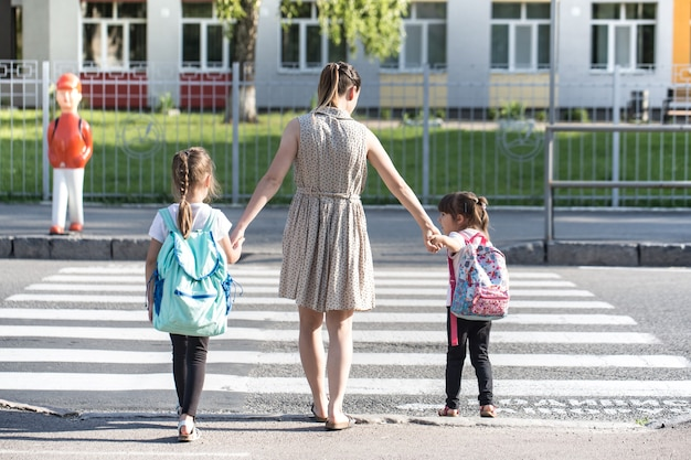 Terug naar schoolonderwijs concept met meisjeskinderen, elementaire studenten, die rugzakken dragen die naar de klas gaan