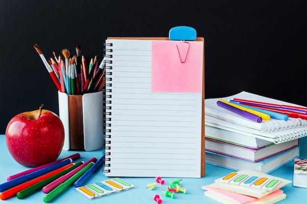 Terug op school, werk, werkplek van een schoolkind briefpapier, notebooks op blauw