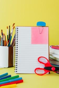 Terug op school, werk, werkplek van een schoolkind briefpapier, notebooks op geel