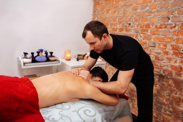 Terug opwarmen. professionele kortharige masseur in zwart uniform die de nek van de vrouw stampt terwijl ze op de buik in de kast ligt