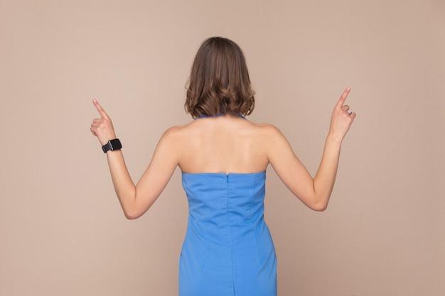Terug, ruggengraat weergave zakenvrouw. met de vingers omhoog. studio opname