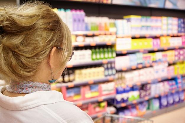 Terug schot van grootmoeder met blond haar winkelen bij de plaatselijke supermarkt, kar vooruit duwen naar huishoudelijke chemie