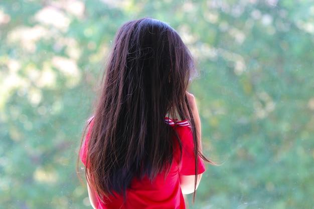 Terug van aziatische meisjeseenzaamheid en huilen wachtend iemand dichtbij het venster ongelukkig op de school