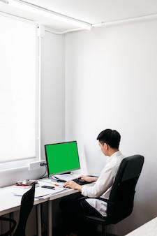 Terug van de man die wit overhemd draagt en op zwarte bureaustoel zit