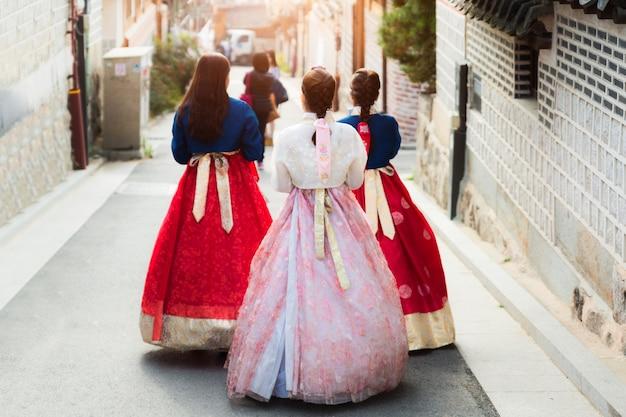 Terug van drie vrouw die hanbok draagt die door het dorp van bukchon hanok in seoel, zuiden loopt