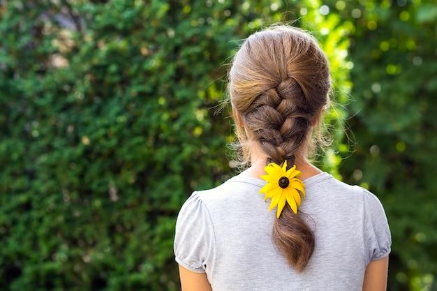 Terug van een vrouw met bloem in haar haar