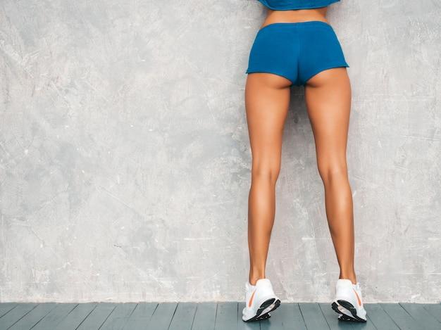 Terug van fitness vrouw in sportkleding op zoek vertrouwen. jong wijfje dat sportkleding draagt. mooi model met perfect gebruinde lichaam. vrouwelijke poseren in de studio in de buurt van grijze muur