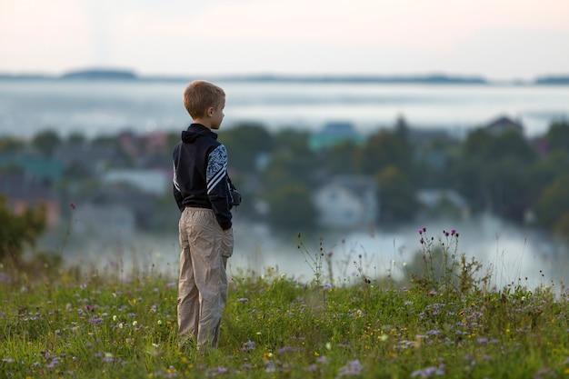 Terug van jong kindjongen alleen op grasrijke heuvelbovenkant op mistig dorp onder groene bomen.