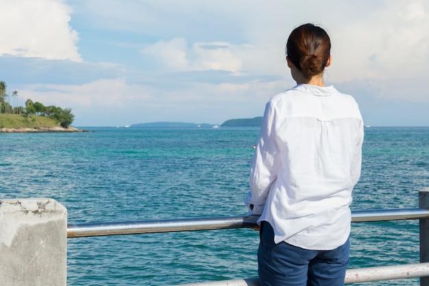 Terug van jonge aziatische dame bij brug die het overzees bekijkt