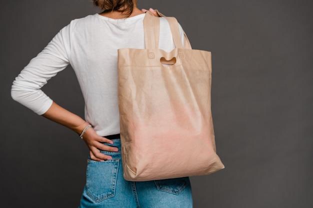Terug van jonge eigentijdse vrouw die in t-shirt en spijkerbroek textiel totalisatorzak op schouder afzonderlijk houden