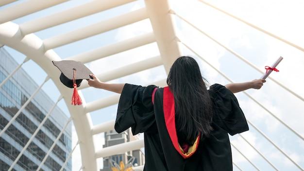 Terug van meisje in zwarte toga's en houd diploma-certificaat met gelukkig afgestudeerd.