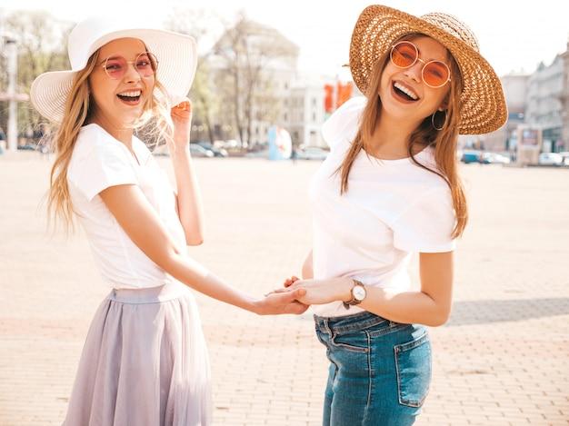 Terug van twee jonge mooie blonde glimlachende hipstermeisjes in de kleren en de hoed van de trendy de zomer witte t-shirt. . paar hand in hand