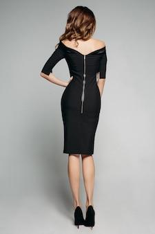 Terug volledige lengte van een prachtig slank model met donkerbruin haar, gekleed in een elegante zwarte jurk met blote schouders en ritssluiting en zwarte hoge hakken. uitsnede op grijs. studio.